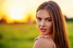 Mooie jonge vrouw op aard over de zomerzonsondergang stock foto