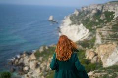 Mooie jonge vrouw op de afgrond van een berg dichtbij het overzees Stock Foto