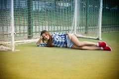 Mooie jonge vrouw op het voetbalgebied royalty-vrije stock foto's