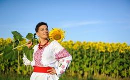 Mooie jonge vrouw op het zonnebloemengebied. Royalty-vrije Stock Foto
