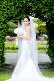 mooie jonge vrouw op huwelijksdag in witte kleding in de tuin Vrouwelijk portret in het park Stock Foto