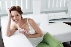 Mooie Jonge Vrouw op Sofa In Living Room Stock Afbeelding