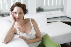 Mooie Jonge Vrouw op Sofa In Living Room Royalty-vrije Stock Fotografie
