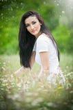 Mooie jonge vrouw op wild bloemengebied Portret van aantrekkelijk donkerbruin meisje met het lange haar ontspannen in aard, openl Royalty-vrije Stock Afbeeldingen
