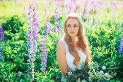 Mooie jonge vrouw over het bloeien lupines stock foto