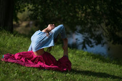 Mooie jonge vrouw in rode rok het praktizeren Yogaasana in aard Royalty-vrije Stock Fotografie