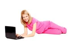 Mooie jonge vrouw in roze dat op de vloer ligt Stock Afbeelding