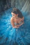Mooie jonge vrouw in schitterende blauwe lange kleding zoals Cinderella met perfecte samenstelling en haarstijl Stock Foto's
