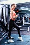 Mooie jonge vrouw in sportkleding die sommige gewichten opheffen stock fotografie