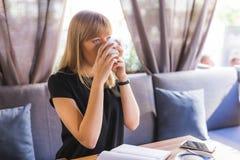 Mooie jonge vrouw terwijl het drinken van thee royalty-vrije stock foto's