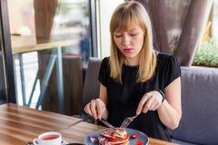 Mooie jonge vrouw terwijl het eten van pannekoeken en het drinken van thee royalty-vrije stock foto