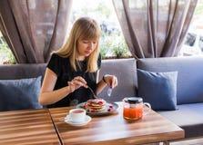 Mooie jonge vrouw terwijl het eten van pannekoeken en het drinken van thee stock foto's