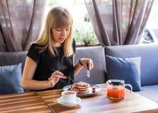 Mooie jonge vrouw terwijl het eten van pannekoeken en het drinken van thee royalty-vrije stock fotografie