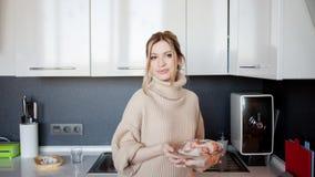Mooie jonge vrouw thuis in de keuken, die een gezonde maaltijd voorbereiden stock foto