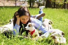 Mooie jonge vrouw in toevallige uitrusting op picknick in park met haar aanbiddelijk de terriërpuppy van hefboomrussell, groen gr Royalty-vrije Stock Afbeelding