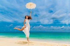 Mooie jonge vrouw in witte kleding met paraplu op een tropisch strand stock foto