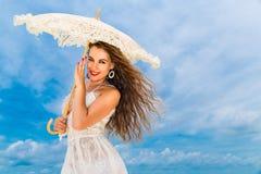 Mooie jonge vrouw in witte kleding met paraplu op een tropisch strand Stock Foto's