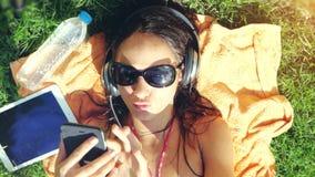 Mooie jonge vrouw in zonnebril die op het gras liggen, luisterend aan muziek en het zingen lied Bovenkant van mening, 3840x2160 stock footage