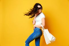 Mooie jonge vrouw in zonnebril, wit overhemd die, jeans met zak stellen Stock Fotografie