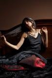 Mooie jonge vrouw in zwarte en rode kledingssitti Royalty-vrije Stock Afbeeldingen