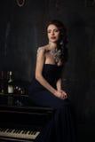 Mooie jonge vrouw in zwarte kleding naast een piano met kandelaberskaarsen en wijn, donkere dramatische atmosfeer van het kasteel stock afbeelding