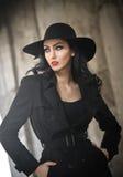 Mooie jonge vrouw in zwarte uitrusting, stedelijk concept Het elegante brunette met hoed het stellen met dient haar zak in, openl Royalty-vrije Stock Afbeelding