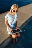 Mooie jonge vrouwelijke blondezitting op strand met laptop smili stock afbeeldingen