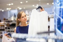 Mooie jonge vrouwelijke klant in een kledingsopslag stock afbeeldingen