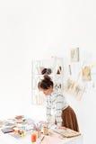Mooie jonge vrouwelijke manierontwerper die in studio werken Stock Afbeelding