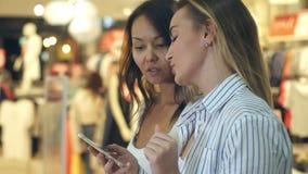 Mooie jonge vrouwelijke shopaholics twee die Internet die op zoek naar kortingen surfen in winkelcomplex lopen stock videobeelden