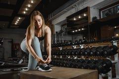 Mooie jonge vrouwen bindende schoenveters op tennisschoenen in de gymnastiek met domoren op achtergrond royalty-vrije stock afbeeldingen