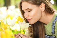 Mooie jonge vrouwen dichtbij tot bloei komende tulpen Stock Fotografie