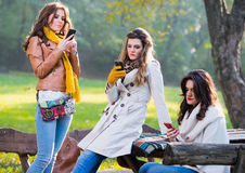 Mooie jonge vrouwen die celtelefoons met behulp van Royalty-vrije Stock Foto