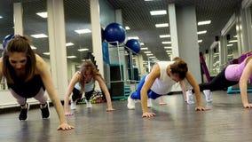 Mooie jonge vrouwen die opdrukoefeningen doen tijdens een training stock video
