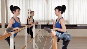 Mooie jonge vrouwen die spleten uitvoeren die zich in de repetitieruimte uitrekken De slanke meisjes bevinden zich voor de spiege stock footage