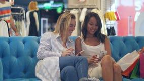 Mooie jonge vrouwen met het winkelen zakken en smartphone in wandelgalerij die hun mannelijke vriend ontmoeten stock footage