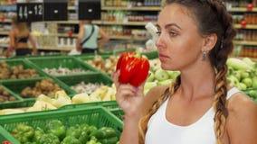Mooie jonge vrouwen ruikende paprika bij de supermarkt stock video