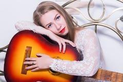 Mooie jonge vrouwen speelmuziek op een bed met geluk en gitaar Stock Afbeelding