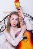 Mooie jonge vrouwen speelmuziek op een bed met geluk en gitaar Stock Foto
