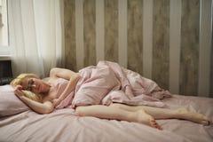 Mooie jonge vrouwenslaap in de slaapkamer stock foto