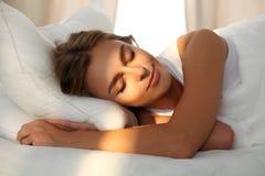 Mooie jonge vrouwenslaap terwijl gelukzalig het liggen in bed comfortabel en Zonnestraaldageraad op haar gezicht Stock Afbeelding