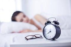 Mooie jonge vrouwenslaap terwijl het liggen in bed comfortabel en gelukzalig op de achtergrond van wekker Royalty-vrije Stock Foto's