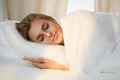 Mooie jonge vrouwenslaap terwijl het liggen in bed comfortabel en gelukzalig Zonnestraaldageraad op haar gezicht Stock Afbeelding