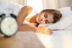 Mooie jonge vrouwenslaap terwijl het liggen in bed comfortabel en gelukzalig Zonnestraaldageraad op haar gezicht Stock Foto's