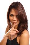 Mooie jonge vrouwenvinger op lippen voor geheim stock foto