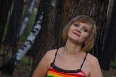 Mooie jonge vrouwenzetel onder de boom Mooie jonge vrouw in openlucht in het houtportret Stock Foto's