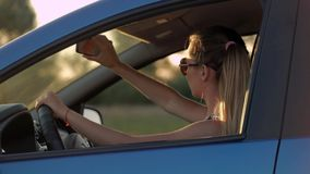 Mooie jonge vrouwenzitting in auto het drijven in de zonsondergang stock videobeelden