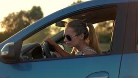 Mooie jonge vrouwenzitting in auto het drijven in de zonsondergang stock footage