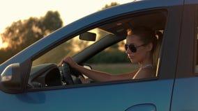 Mooie jonge vrouwenzitting in auto het drijven in de zonsondergang stock video