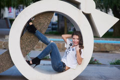 Mooie jonge vrouwenzitting in de architecturale cirkel stock afbeeldingen